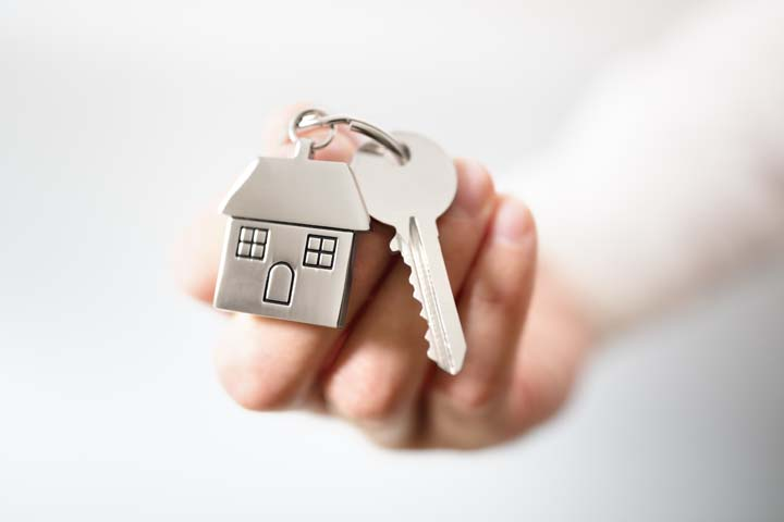 Holding house keys on house shaped keychain concept for buying a